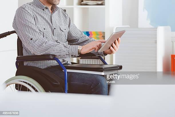 Places homme assis dans un fauteuil roulant et à l'aide de tablette numérique