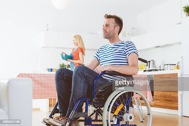 Disabled man sitting in a wheelchair at home