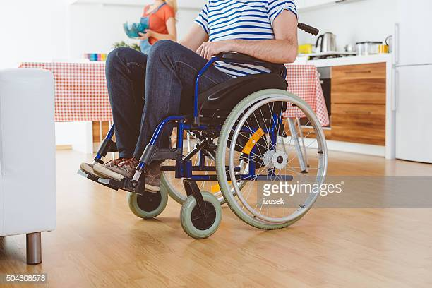 Disabled man sitting in a wheelchair, close up of legs
