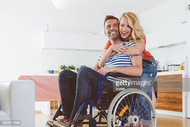 Behinderten Mann sitzt im Rollstuhl, seine Frau umarmt ihn