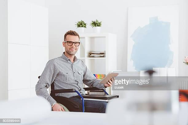 Behinderten Mann sitzt im Rollstuhl, die holding digital tablet