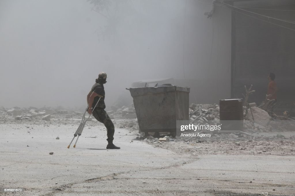 A disabled man tries to escape from explosion site after Assad Regime's forces strike over the de-conflict zone, Ein Tarma Town of Eastern Ghouta region of Damascus, Syria on August 22, 2017.