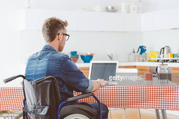 Disabled man using a laptop in the kitchen