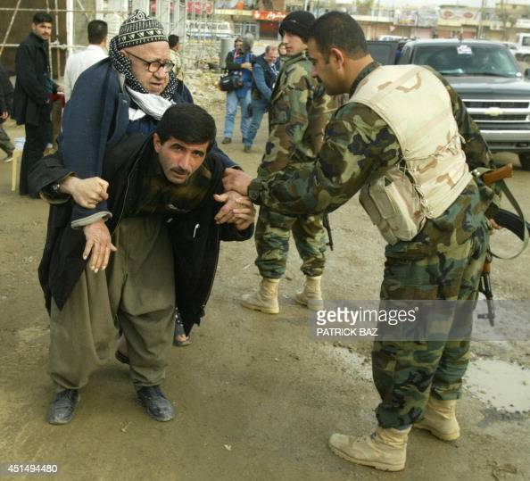 Disabled Mohammed Karim Khader is carried on the shoulder of a man on his way to cast his vote in the northern Kurdish city of Suleimaniya 30 January...