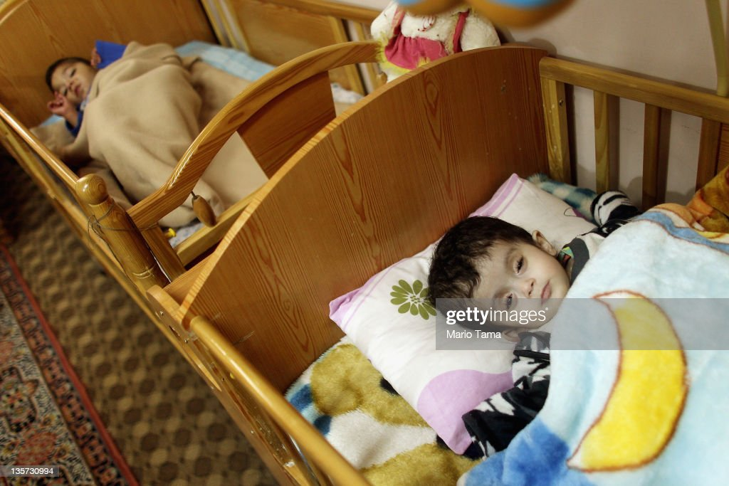 Disabled orphan Rasha, 2, rests in the orphanage where she lives on December 13, 2011 in Baghdad, Iraq. Rasha was abandoned at birth by her parents at the hospital. Iraq's health care system remains in shambles following two decades of war and economic sanctions. Following the 2003 U.S. invasion, thousands of physicians fled the country while others were killed. Some physicians have since returned but there is still a critical shortage of doctors. Iraq is transitioning nearly nine years after the 2003 U.S. invasion and subsequent occupation. American forces are now in the midst of the final stage of withdrawal from the war-torn country. At least 4,485 U.S. military personnel have died in service in Iraq. According to the Iraq Body Count, more than 100,000 Iraqi civilians have died from war-related violence.