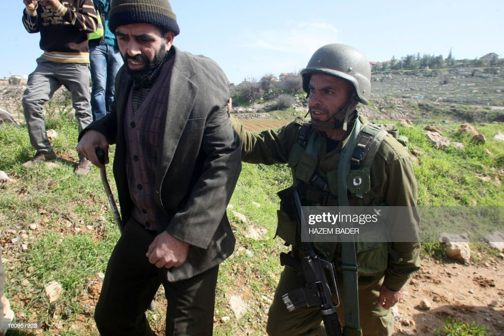 A disabled Palestinian protester is pushed away by an Israeli soldier during a demonstration in protest with the closure of an entrance leading to the West Bank city of Hebron on February 8, 2013 in Hebron.