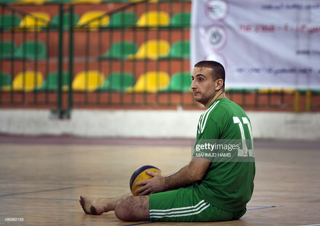 Disabled Palestinian volley ball player Hani Abu al-Aish sits on the floor as he warms up prior to a game in Gaza City on November 19, 2013. Disabled players from the Islamic Society and the Red Crescent team most of them badly injured during Israel's assault on the Gaza Strip on November 14, 2012 played against eachothers marking the first anniversary of the war. AFP PHOTO / MAHMUD HAMS