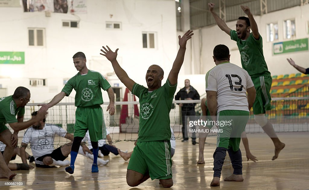 Disabled Palestinian volleyball players from the Islamic Society celebrate as they won over the Red Crescent, during a game in Gaza City on November 19, 2013. Disabled players, most of them badly injured during Israel's assault on the Gaza Strip on November 14, 2012 showed their skills as they marked the first anniversary of the war. AFP PHOTO / MAHMUD HAMS
