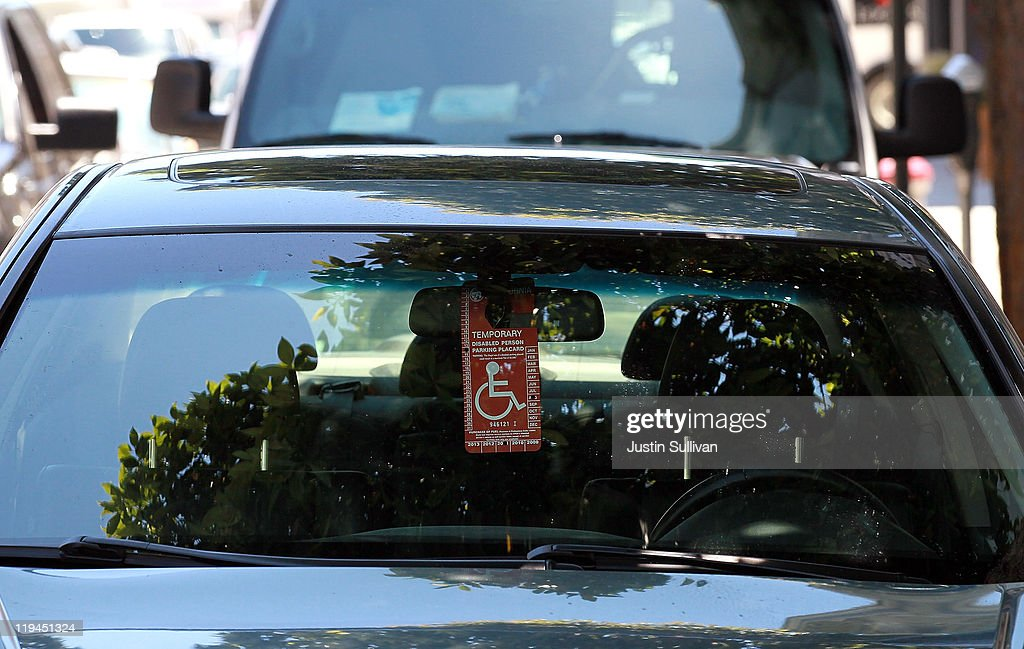 A disabled parking placard hangs from a car's rearview mirror on July 20, 2011 in San Francisco, California. The California DMV says that is has sent out nearly 60,000 disabled parking placards to dead people since the DMV only checks state death records every two years. The disabled parking placards allow handicapped motorists to park for free and in designated parking spots.