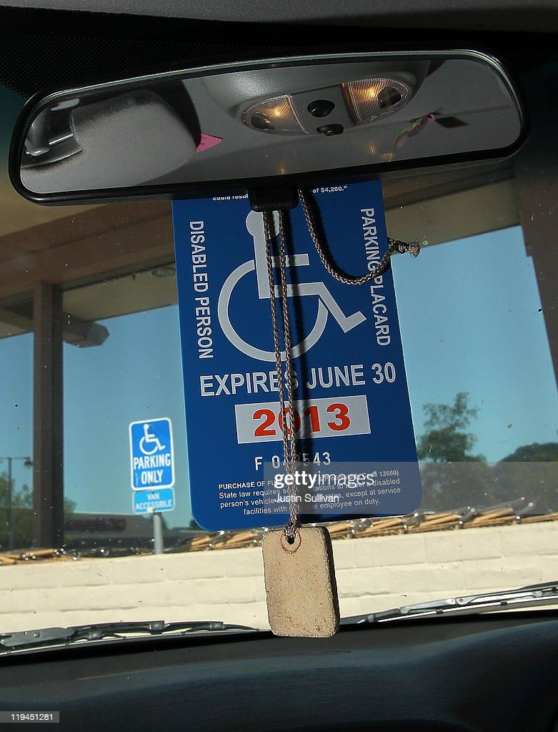 A disabled parking placard hangs from the rearview mirror of a car in a Safeway parking lot on July 20, 2011 in San Anselmo, California. The California DMV says that is has sent out nearly 60,000 disabled parking placards to dead people since the DMV only checks state death records every two years. The disabled parking placards allow handicapped motorists to park for free and in designated parking spots.