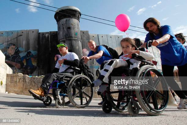 Disabled participants pass Israel's controversial separation barrier which divides the West Bank from Jerusalem in the biblical West Bank town of...