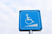 Disabled people wheelchair slope way sign for handicap support with gray sky in background