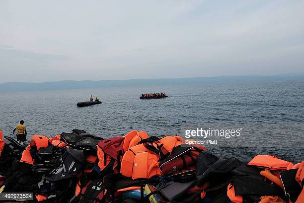 A disabled raft is pulled ashore onto the island of Lesbos which is littered with life preservers on October 16 2015 in Sikaminias Greece Dozens of...