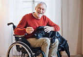 A disabled senior man in wheelchair indoors playing with a pet dog at home. Copy space.