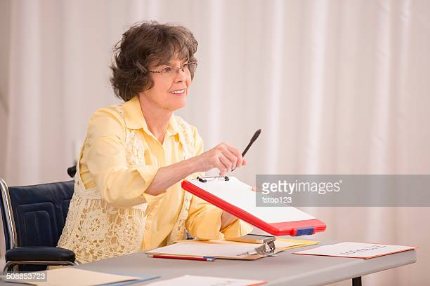 Disabled senior woman at conference or voter registration table.