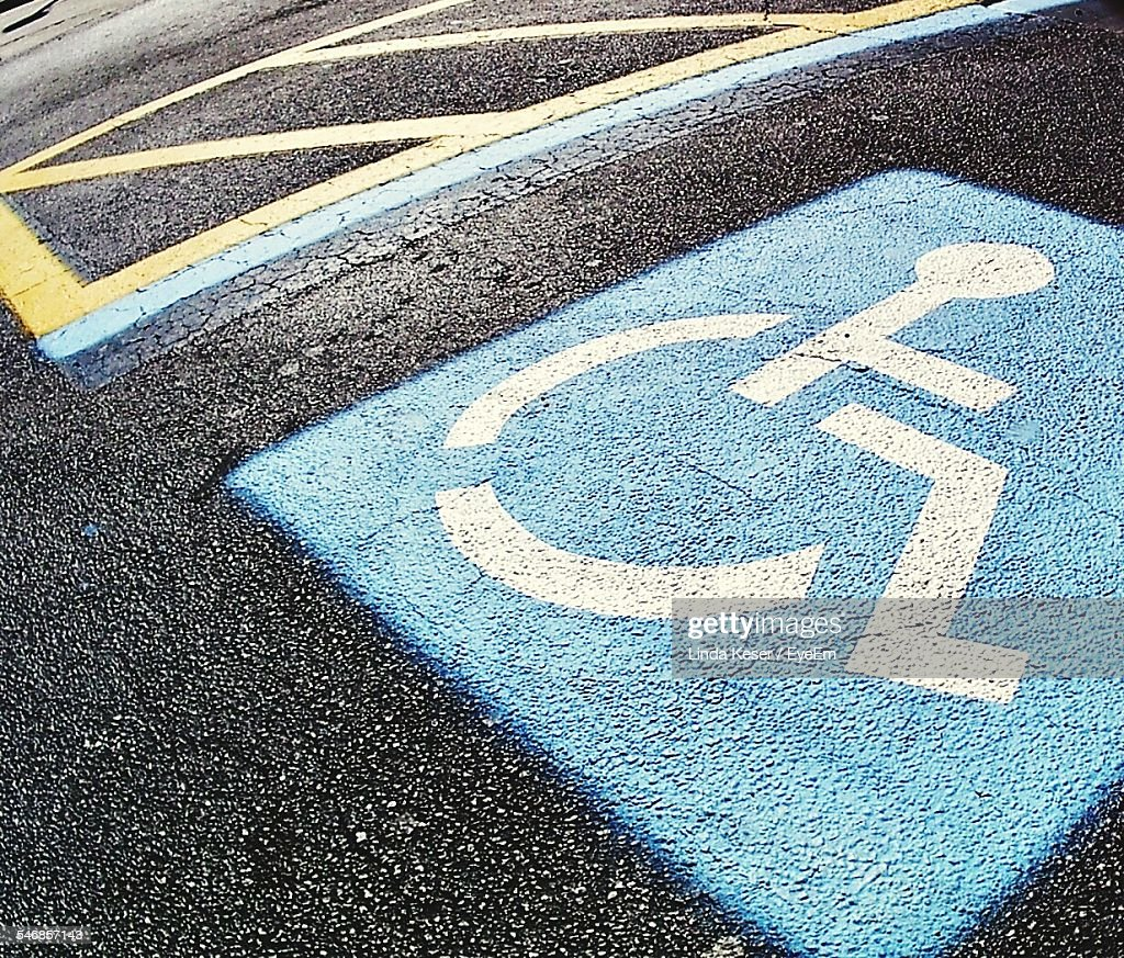 Disabled Sign On Road At Parking Lot
