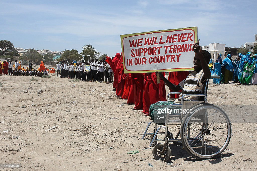 A disabled Somali boy holds a poster stating that he will never support terrorism in his country during an anti Alshabab rally in Mogadishu on...
