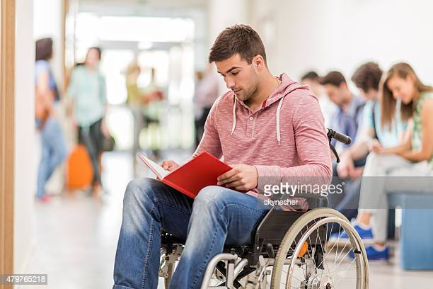 Disabled student reading a book in the university hall.