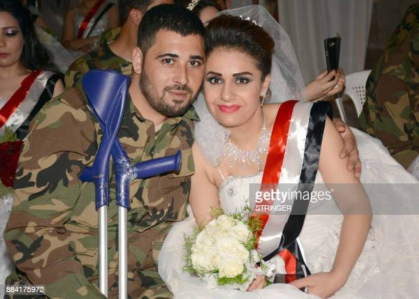 A disabled Syrian veteran poses for a picture with his bride who is wearing a sash bearing the colours of the Syrian flag during a mass wedding for...