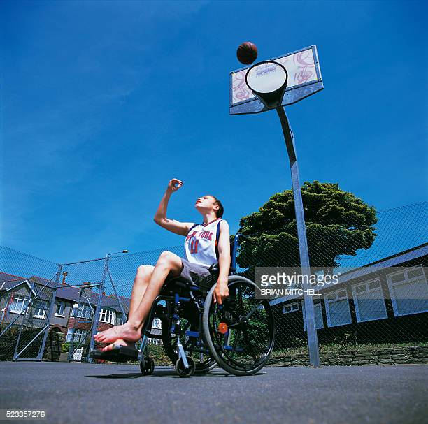 Disabled teenage boy in a wheelchair playing out door basketball