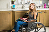 Portrait of a beautiful young woman on a wheelchair doing house chores in the kitchen and smiling