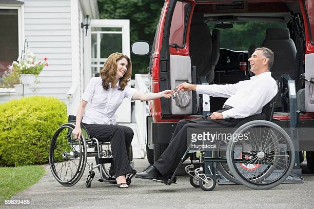 Disabled woman giving a car key to her husband sitting in a wheelchair
