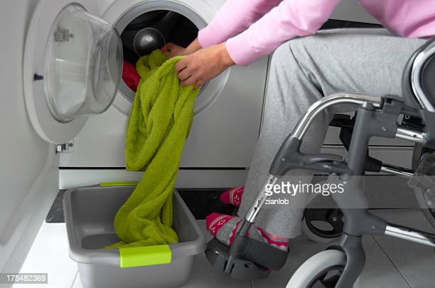 Disabled woman in a wheelchair doing laundry.