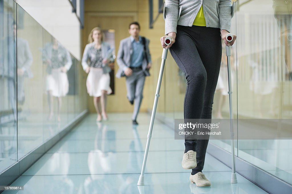 Disabled woman walking with a man and a woman running behind her