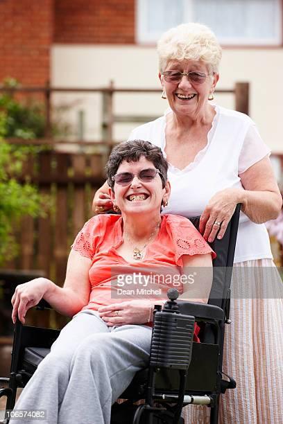 Behinderte Frau mit einer Pflegekraft reisen im Garten
