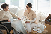 A disabled old woman on a wheelchair holding hand of a tender professional medical assistant during tea time in a living room of luxury retirement home