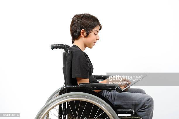 Disabled young boy looking at digital tablet