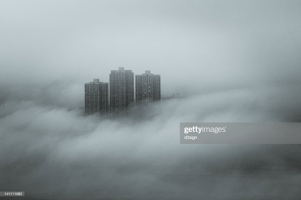 Disappearing skyscraper by fog and cloud : Stock Photo