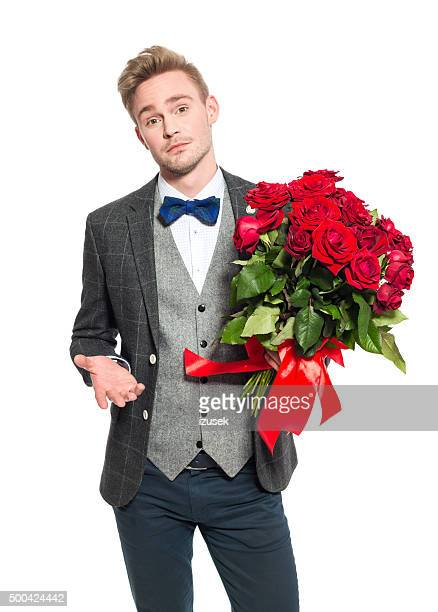 Disappointed blonde businessman holding bunch of roses