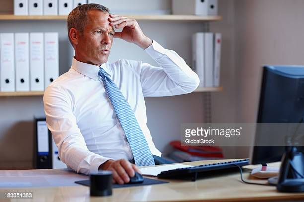 Disappointed businessman looking at computer screen