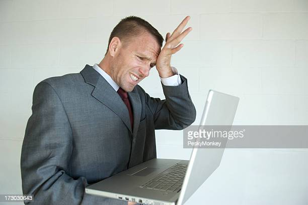 Disappointed Businessman Smacking His Head After Computer Mistake