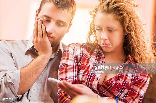 Disappointed couple looking at pregnancy test.