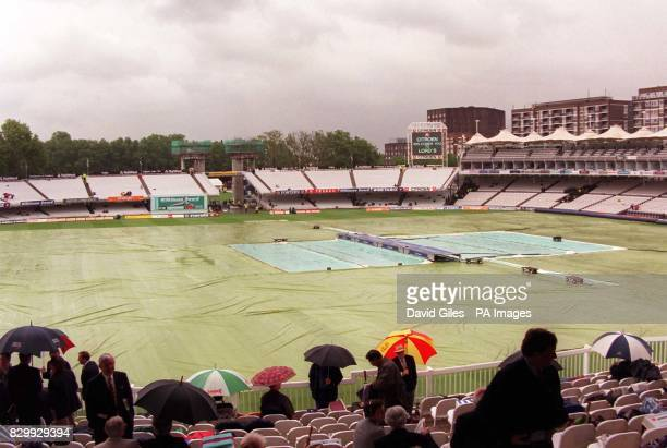 Disappointed cricket fans huddle beneath umbrellas next to the tarpaulin covered pitch at Lord's today as black rain filled clouds continue to drench...