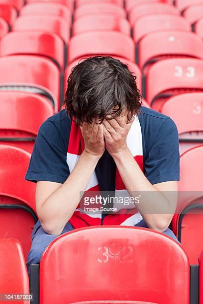 Decepcionado ventilador de fútbol en estadio vacío