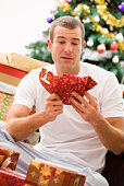 Disappointed man unwrapping presents