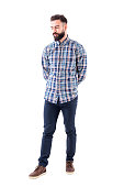 Disappointed skeptical bearded hipster with hands on back looking down. Full body isolated on white background.