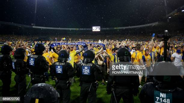 Disappointed supporters of Braunschweig enter the pitch after German Bundesliga relegation second leg football match between Eintracht Braunschweig...