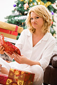 Disappointed woman unwrapping presents