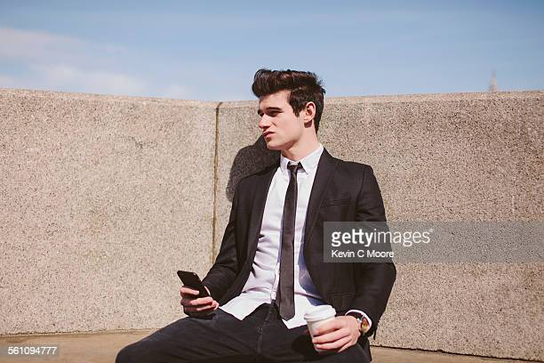 Disappointed young businessman on city seat with smartphone