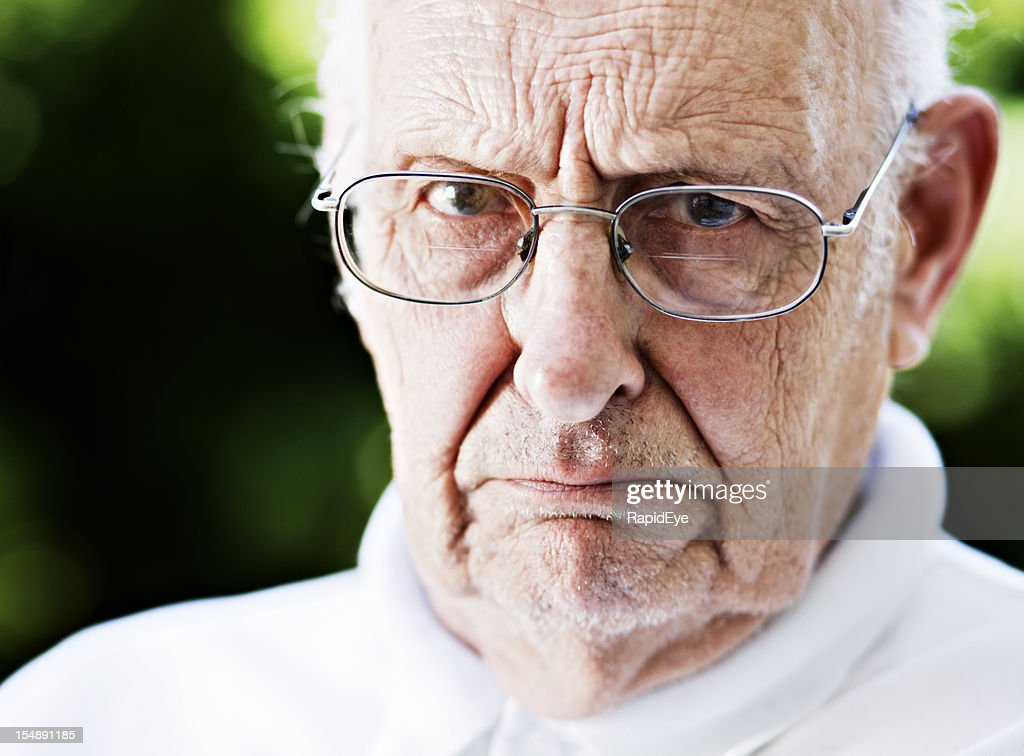 Disapproving old man glares at camera over his glasses, frowning