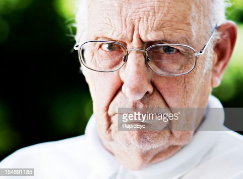 Nicht sehr erfreut darüber Alter Mann glares in die Kamera über seine Brille, Stirn runzeln