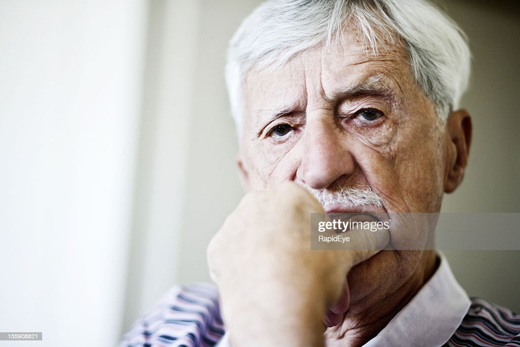 Disapproving old man stares out, hand on chin