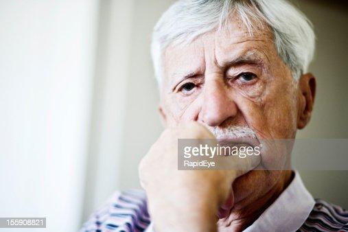 old man sieht nicht sehr erfreut darüber, hand am Kinn