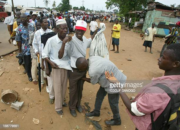 A disarmed rebel soldier checks people passing to the LURD controlled port of Duala area 17 August 2003 in Monrovia where Nigerian troops of the...