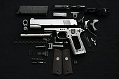 Disassembled handgun on black background