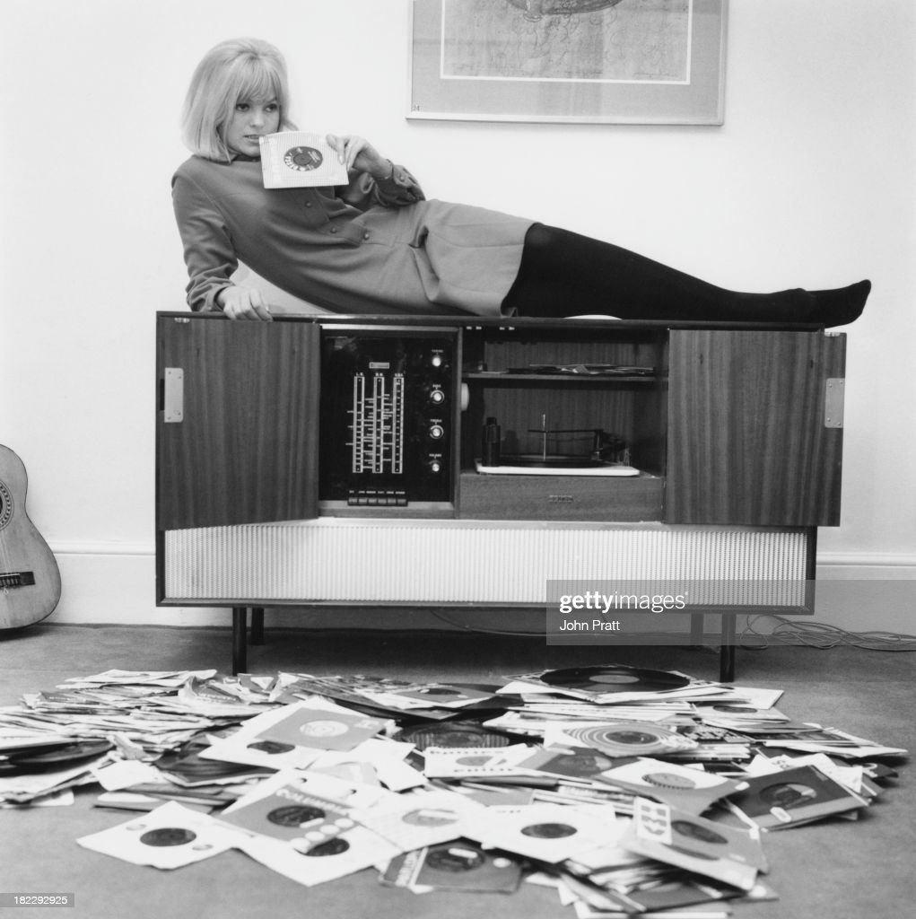 Disc jockey and presenter of the Rediffusion TV music show 'That's For Me', Anne Nightingale, reclining on her stereogram at her home in Brighton, Sussex, 14th December 1964.